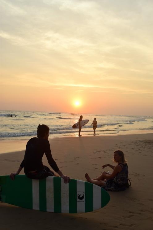 Solen går ner över surfare och strand.